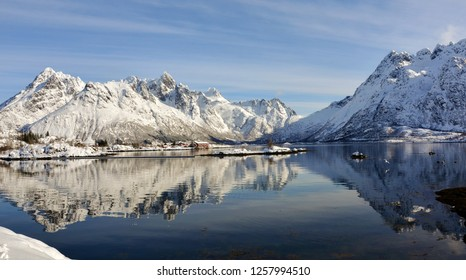 Photo of  alpine mountains reflected in a near-quiet fjord. The landscape is covered in snow, and a cluster of houses can be seen on a small peninsula