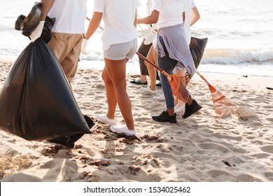 Photo of altruistic volunteers people cleaning beach from plastic with trash bags at seaside