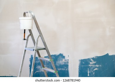 Photo of aluminum stairs for higher work with white bucket of putty coating against wall on reconstruction