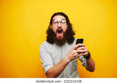 Photo of amazed bearded hioster man in shirt with glasses