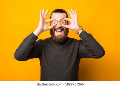 Photo of amazed bearded man holding bit coin over eyes