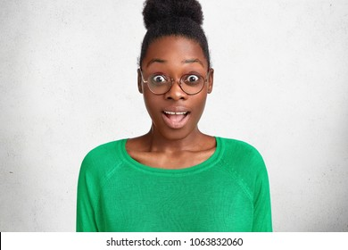 Photo of amazed dark skinned female looks with bated breath and unexpected expression, wears casual green sweater and round glasses, recieves surprise from husband. Emotional African young woman