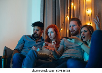 Photo of amazed four friends watching a movie at home.