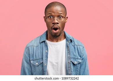 Photo of amazed middle aged African American male has surprised expression, hears horrified news, wears casual denim shirt, poses against pink background. People, emotions and ethnicity concept