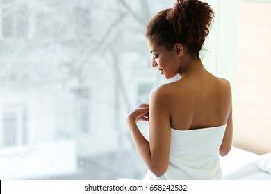 Photo of amazing young african woman dressed in towel standing at home near window and looking aside.