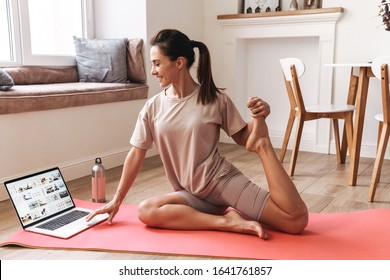 Photo of amazing young beautiful brunette fitness woman make stretching exercises indoors at home near laptop computer.