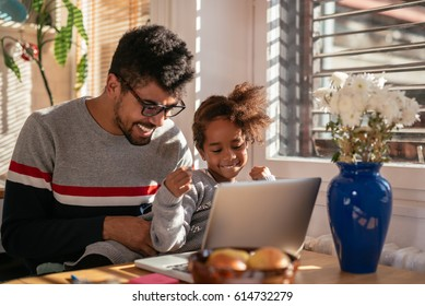 Photo of an american father and daughter playing on computer indoors.