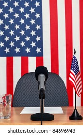 Photo of an American themed conference desk with microphone and flags.