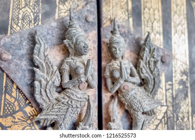 Photo of Ancient Thai goddesses as wood sculptures on the Thai temple door in Ayudhaya Thailand, February 18, 2018