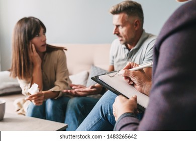 Photo of angry irritated couple man and woman having conversation with psychologist on therapy session in room