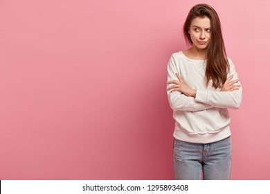 Photo of angry woman concentrated aside, has arms folded, gloomy expression, dark straight hair, wears casual clothes, isolated over pink studio wall with empty space for your promotional content