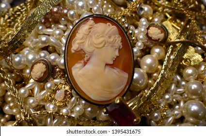 A photo of a an antique carved lady cameo with pearls gold,
