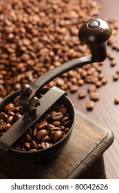 Photo of an antique coffee grinder with coffee beans in the blurred background.