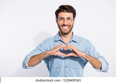 Photo of arabian guy toothy beaming smile making heart figure with fingers romance date invitation wear specs casual denim shirt isolated white color background