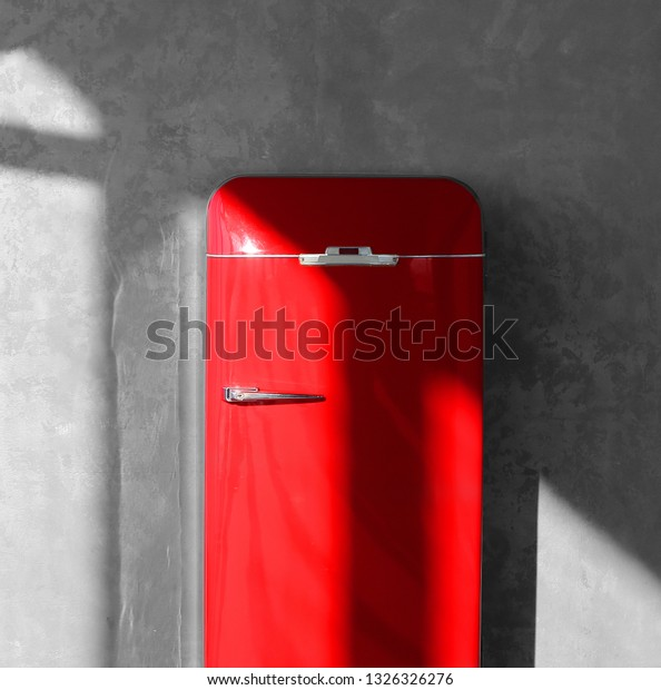 Photo art background unusual red retro fridge on sunny background