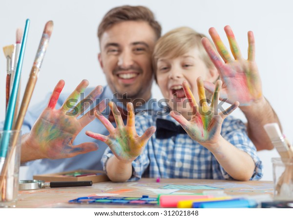 Photo of art teacher and schoolboy with color on hands