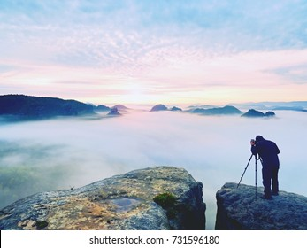Photo artist in work. Photographer in rocky mountains. Traveler takes photos of dreamy majestic landscape, sunset at horizon