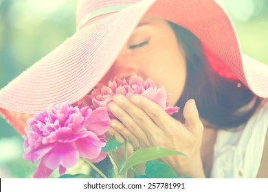 photo with artistic blurring and blur effect. special defocused effect. Vintage toning. film retro style. outdoor closeup portrait of a beautiful woman. lady in a hat in the park with flowers