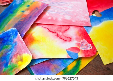 A photo of the artistic hand drawn abstract wet watercolor background, waldorf colorful template and a pencil. A lesson of drawing in Waldorf Steiner school, kindergarten