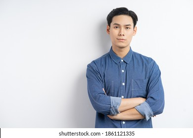 Photo of an Asian businessman standing with his arms crossed and smiling on a white background