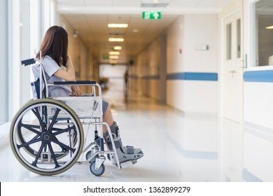 Photo of Asian female on wheel chair with orthopedic walking cast in hospital. Selective focus at the leg with shallow DOF and blurred background with copy space. The wheelchair for disability person.