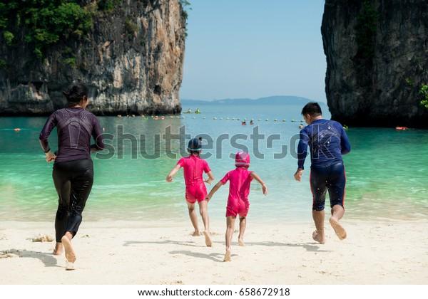 夏のタイ・プーケットで海辺を駆け下るアジアの幸せな家族の写真。夏、旅行、休暇、ホリデーのコンセプト。