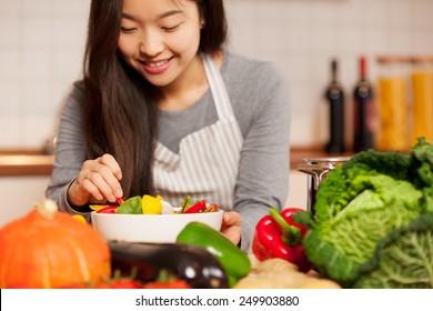 Foto einer asiatischen jungen Frau, die zu Hause einen bunten Salat in der Küche komponiert