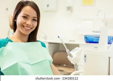 Foto einer asiatischen jungen Frau, die beim Zahnarzt sitzt und sich der Kamera nähert