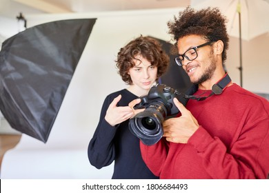 Photo assistant with professional photographer and SLR camera