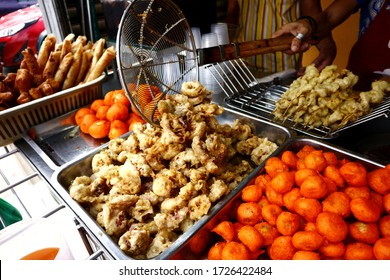 Photo of assorted deep fried street food sold at a food cart along a sidewalk