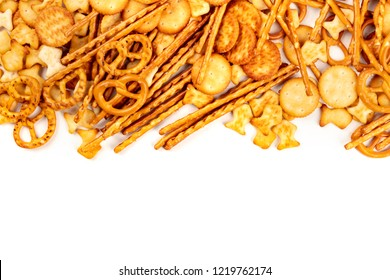 A photo of an assortment of salt crackers, sticks, pretzels, and fishes, shot from the top on a white background with copy space. Salty party snacks mix