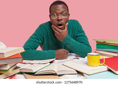 Photo of astonished black young man holds chin, stares in disbelief, has many opened books around table, drinks coffee or tea, isolated over pink studio background. Ethnicity and studying concept