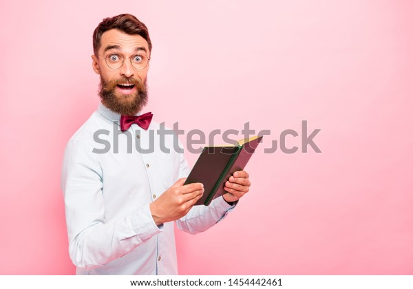 Photo of astonished excited cheerful rejoicing positive glad scientist genius holding opened paper literature in hands isolated pastel background