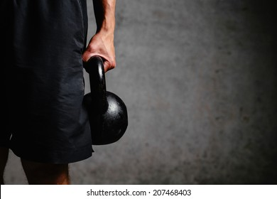 Photo of an athlete arm holding a kettlebell