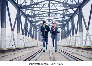 Photo of an athlete friends running on the train bridge in the morning.