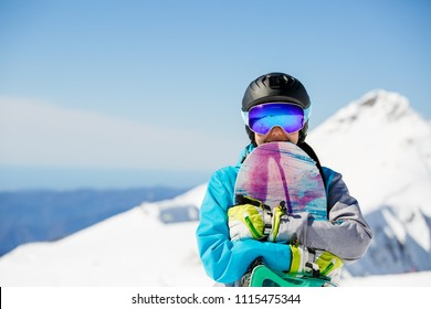 Photo of athlete in helmet with snowboard on snowy hill