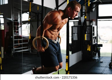 Photo of an athlete working out his muscles on rings
