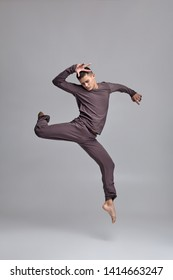 Photo of an athletic man ballet dancer dressed in a gray tracksuit, making a dance element against a gray background in studio.