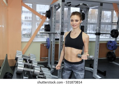 photo of athletic young girl doing a fitness workout with dumbbells in the gym