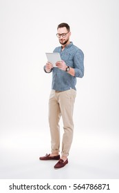 Photo of attractive bearded man wearing glasses dressed in blue shirt using tablet computer isolated over white background.