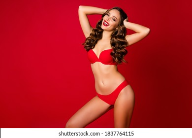 Photo of attractive beauty curly lady advertising underwear novelty sensual slim fit body bright pomade arms on head wear brassiere panties isolated red color background