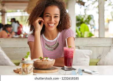 Photo of attractive black woman has Afro hairstyle, dressed in casual t shirt, smiles broadly at camera, rejoices meeting with colleague in cozy cafe, drinks fresh smoothie, likes exotic food