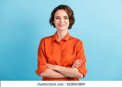 Foto von attraktiven charmanten Dame süße Bettkopfhairdo Arme überquerte selbstbewusste Person freundlich lächelnd gute Laune tragen orangefarbenes Büroshirt einzeln blauer Hintergrund