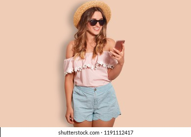 Photo of attractive cheerful woman dressed in fashionable summer clothes, uses modern cellular for online comunication, wears trendy sunglasses, isolated over beige background. Technology, rest
