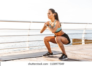 Photo of attractive concentrated woman 20s in tracksuit squatting near sport mat during workout on boardwalk at seaside