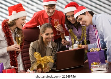 Photo of attractive co-workers with champagne in hands looking at laptop display