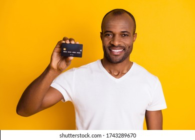 Photo of attractive dark skin guy hold plastic credit card showing novelty bank offer proposition free money wear casual white t-shirt isolated bright yellow color background