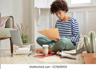 Photo of attractive dark skinned young corporate businesswoman checks monthly income on paper documents, sits crossed legs on floor, studies resume of new employee, cozy home interior, prepres report