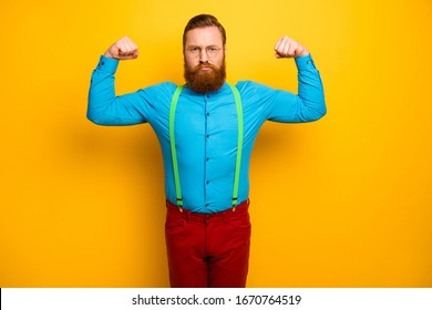 Photo of attractive funny guy seriously raise fists arms presenting perfect shape biceps sports addicted wear blue shirt green suspenders red pants isolated yellow color background