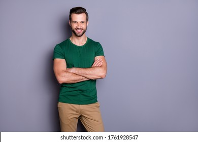 Photo of attractive guy business man macho appearance neat hairdo bristle smiling beaming good mood arms crossed wear casual green t-shirt pants isolated grey color background